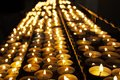 Many beautiful lit candles in a row glowing with a golden yellow light Royalty Free Stock Photo