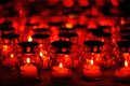Many candles burning in red candle holders at night Royalty Free Stock Photo