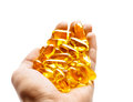 Many capsules Omega 3 in hand on white background Royalty Free Stock Photo