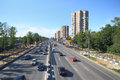 Many cars goes on wide road in large city sunny summer day work is underway to expand prospect Stock Photos