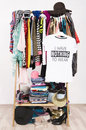 Many clothes on the rack with a t shirt saying nothing to wear close up cluttered wardrobe colorful and accessories and Stock Image