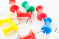 Many color pin push on calendar page. Royalty Free Stock Photo
