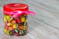 stock image of  Many colorful candies in closed glass jar with pink ribbon on it