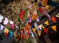 Many colorful flags under the ceiling of the old temple. Garlands in a buddhist temple Royalty Free Stock Photo