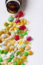 Many colorful medicines spilling out of a bottle on white Stock Photography