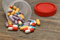 Many Colorful Pills And Capsules Dropped On Wooden Background Royalty Free Stock Photo