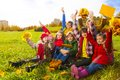 Many friends sit on autumn lawn large group of kids boys and girls sitting in the grass in clothes with maple leaves bouquets and Royalty Free Stock Images