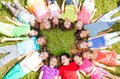 Many group on the grass kids laying in a circle in with happy faces shoot from above Stock Images