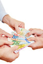 Many hands pulling on Euro money Royalty Free Stock Image