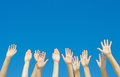 Many hands raised up against the blue sky Stock Photography
