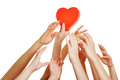 Many hands reaching for red heart as symbol dating Stock Photos