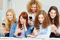 Many happy girls using social media their smartphones school Stock Images