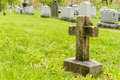Many headstones in a cemetery with cross the foreground Royalty Free Stock Image