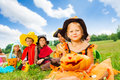 Many kids in halloween costumes sitting close sit on the grass with girl hat holding pumpkin Royalty Free Stock Photo