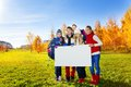 Many kids hold white board group of happy teen standing in autumn park with blank poster for adding text Stock Image