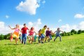 Many kids running in the field boys and girls large group park on sunny summer day casual clothes Stock Images