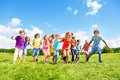 Many kids running large group of friends boys and girls in the park on sunny summer day in casual clothes Stock Image