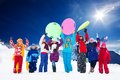 Many kids and snow activities row of large group of friends boys girls standing together outside in waiving hands holding sled Stock Images