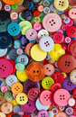 Many mixed brightly coloured sewing or clothing buttons filling the frame Stock Image