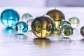 Many multicolored glass balls on a wooden surface. Royalty Free Stock Photo