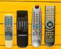 Many obsolete TV remotes on a yellow rustic wooden table. Top view. Royalty Free Stock Photo