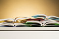 Many open books different on top of a white desk with a warm background and copy space Stock Photo