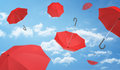 Many open red umbrellas falling from the blue sky dotted with clouds.