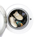 Many pairs of dirty sneakers in the washing machine. Royalty Free Stock Photo