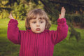 So many problems little girl standing in the park with her hands up indicating her worries Stock Photo