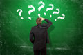 Many questions man in front of a green chalk board with question marks Stock Photo