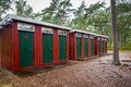 Many red and green wooden outhouse toilets in a row in a forest park. Royalty Free Stock Photo