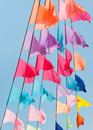 Many small triangular colorful flags flying blue sky Royalty Free Stock Photos