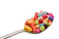 Many tablets on spoon colorful pills a symbolic photo for addiction and abuse of drugs Royalty Free Stock Photos