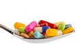 Many tablets on spoon colorful pills a symbolic photo for addiction and abuse of drugs Stock Image