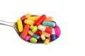 Many tablets on spoon colorful pills a symbolic photo for addiction and abuse of drugs Stock Photos