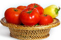 Many tomatoes and pepper in a basket straw Stock Images