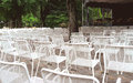 Many unoccupied street chairs in front of stage in autumn rainy day white steel park Royalty Free Stock Photography