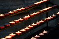 Many wax candles lit by old faithful candlestick in church with Royalty Free Stock Image