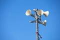 Many white loudspeakers against cloudy blue sky Stock Photography