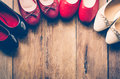 Many women`s shoes are laid on wooden floors.