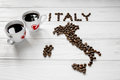 Map of the Italy made of roasted coffee beans laying on white wooden textured background with two cups of coffee Royalty Free Stock Photo
