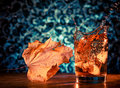 Maple leaf with splashing whiskey big splash ice cubes in glass wirh at abstract background Stock Image