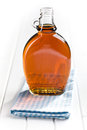 Maple syrup in glass bottle on white wooden table Stock Image