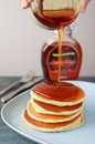 Maple syrup pouring onto pancakes. Royalty Free Stock Photo