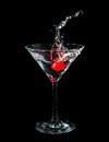 Maraschino cherry dropped in cocktail glass with fluid isolated on black Stock Photos