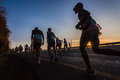 Marathon runners close up silhouettes sunrise photo image shadowed and silhouetted in color against the morning on the fields hill Royalty Free Stock Photo
