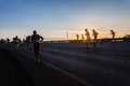 Marathon runners hill climb contrasts sunrise close up photo image shadowed and silhouetted in color against the morning on the Royalty Free Stock Image