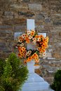 Marble cross in cemetery a or graveyard with a white and floral wreath tinos greek island greece Stock Images