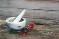 Marble mortar and pestle on old wooden table. Small glass jar wi Royalty Free Stock Photo