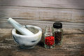 Marble mortar and pestle on old wooden table. Small glass jars w Royalty Free Stock Photo